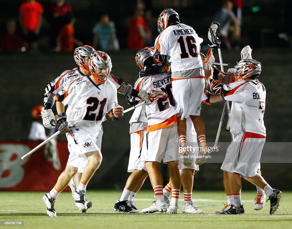 Chris Bocklet #10 of the Denver Outlaws is mobbed by teammates after scoring the game-winning goal in overtime against the Boston Cannons at Harvard Stadium on May 10, 2014 in Boston, Massachusetts.