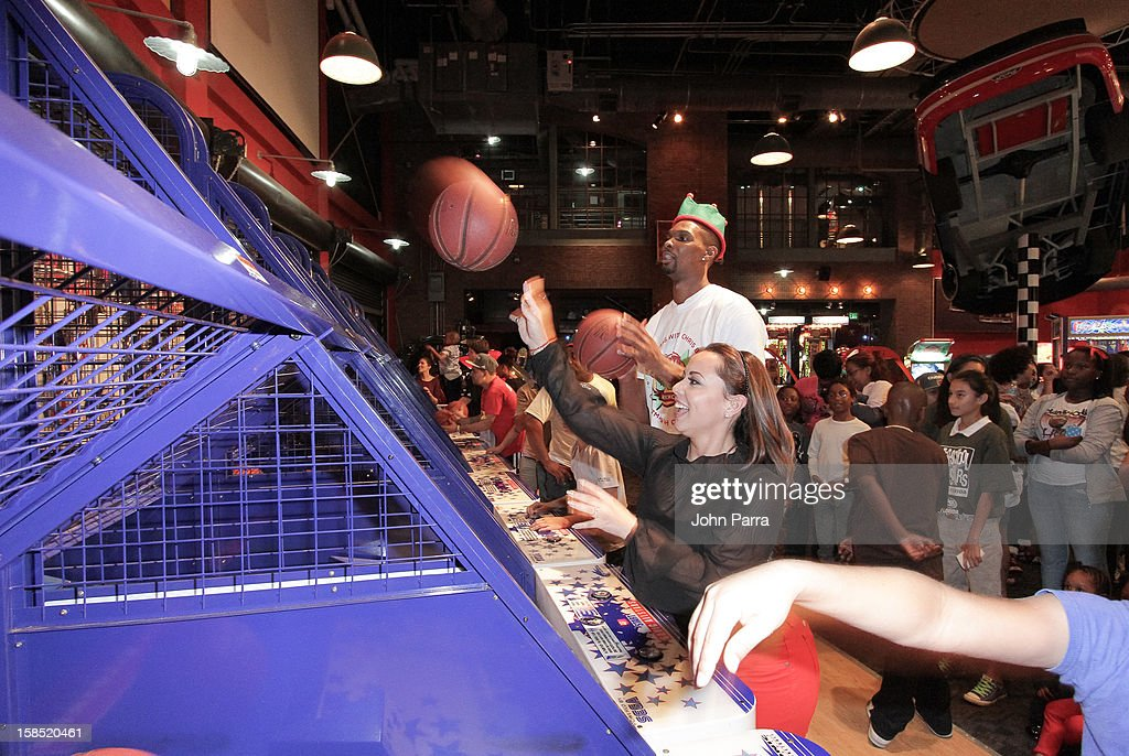Chris Bosh and Adrienne Bosh playing ball during the Christmas With Chris Bosh At 'Santa Bosh's Workshop at Game Time at Sunset Place on December 17, 2012 in Miami, Florida.
