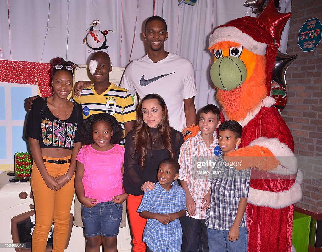 Chris Bosh and Adrienne Bosh poses for picture with the Make-A-Wish foudation kids the 'Santa Bosh's Workshop' Celebration at Game Time at Sunset Place on December 17, 2012 in Aventura, Florida.