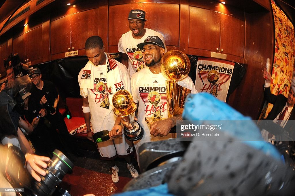 Chris Bosh #1 (L) and Dwyane Wade #3 (2nd L) pose with LeBron James #6 of the Miami Heat as he holds both trophies in a locker room after winning Game Five of the 2012 NBA Finals between the Miami Heat and the Oklahoma City Thunder at American Airlines Arena on June 21, 2012 in Miami, Florida.