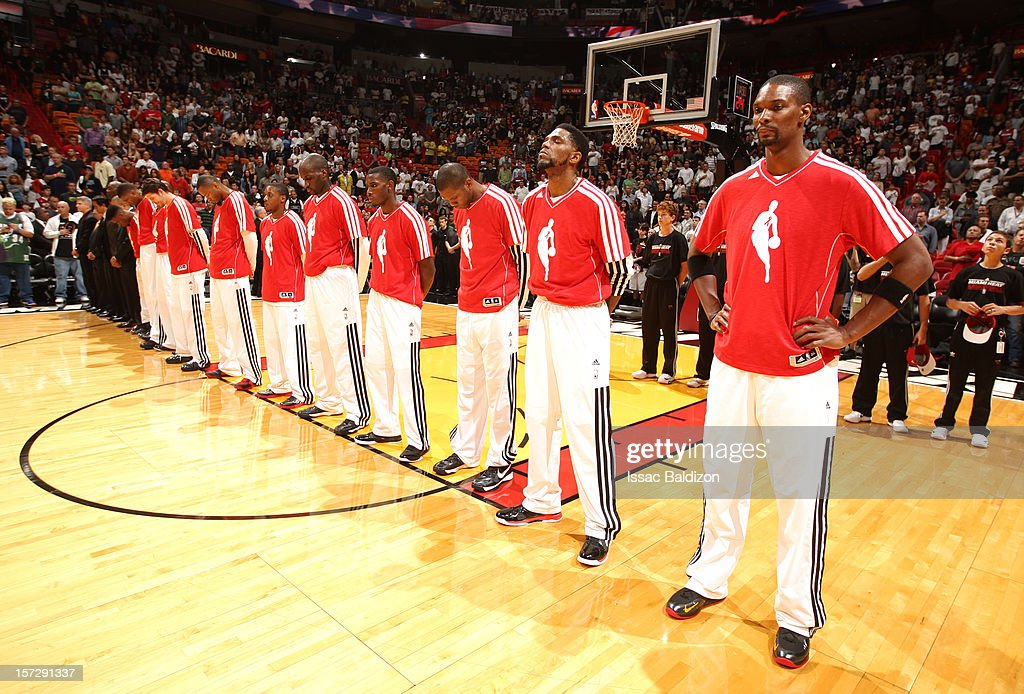 Chris Bosh #1 and the Miami Heat players line up while wearing the red sweatshirts to recognize World AIDS day during a game between the Brooklyn Nets and the Miami Heat on December 1, 2012 at American Airlines Arena in Miami, Florida.