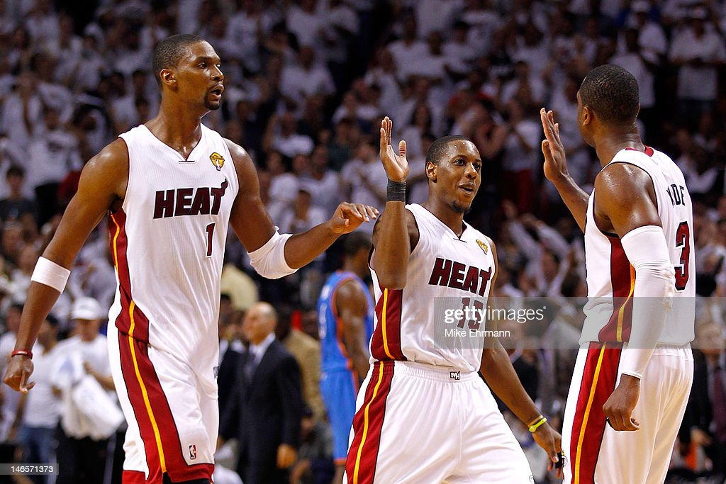 Chris Bosh #1, Mario Chalmers #15 and Dwyane Wade #3 of the Miami Heat celebrate in the fourth quarter against the Oklahoma City Thunder in Game Four of the 2012 NBA Finals on June 19, 2012 at American Airlines Arena in Miami, Florida.