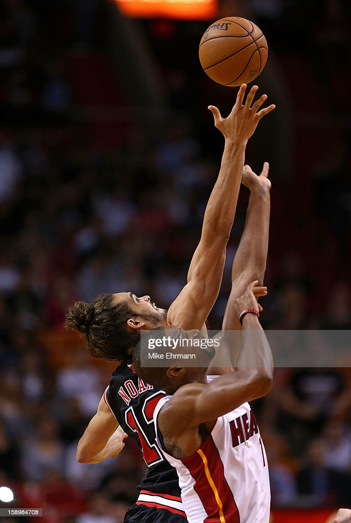 Chris Bosh #1 of the Miami Heat and Joakim Noah #13 of the Chicago Bulls fight for a jump ball during a game at AmericanAirlines Arena on January 4, 2013 in Miami, Florida.