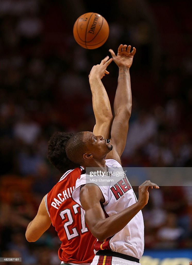 Chris Bosh #1 of the Miami Heat and Zaza Pachulia #27 of the Milwaukee Bucks go up for a jump ball during a game at American Airlines Arena on April 2, 2014 in Miami, Florida.
