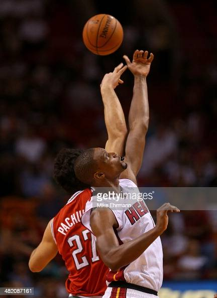 Chris Bosh of the Miami Heat and Zaza Pachulia of the Milwaukee Bucks go up for a jump ball during a game at American Airlines Arena on April 2 2014...