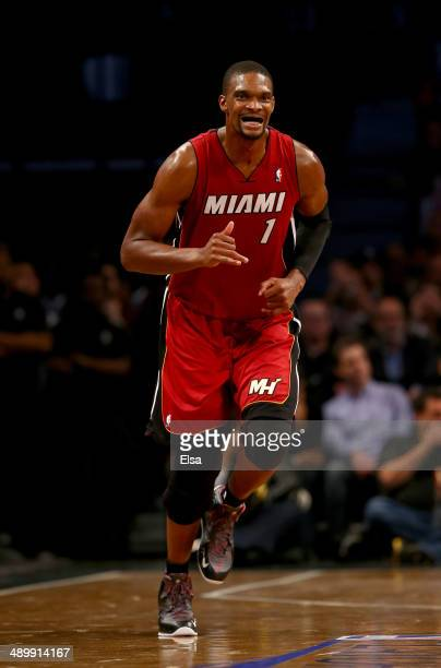 Chris Bosh of the Miami Heat celebrates a three pointer in the fourth quarter against the Brooklyn Nets in Game Four of the Eastern Conference...