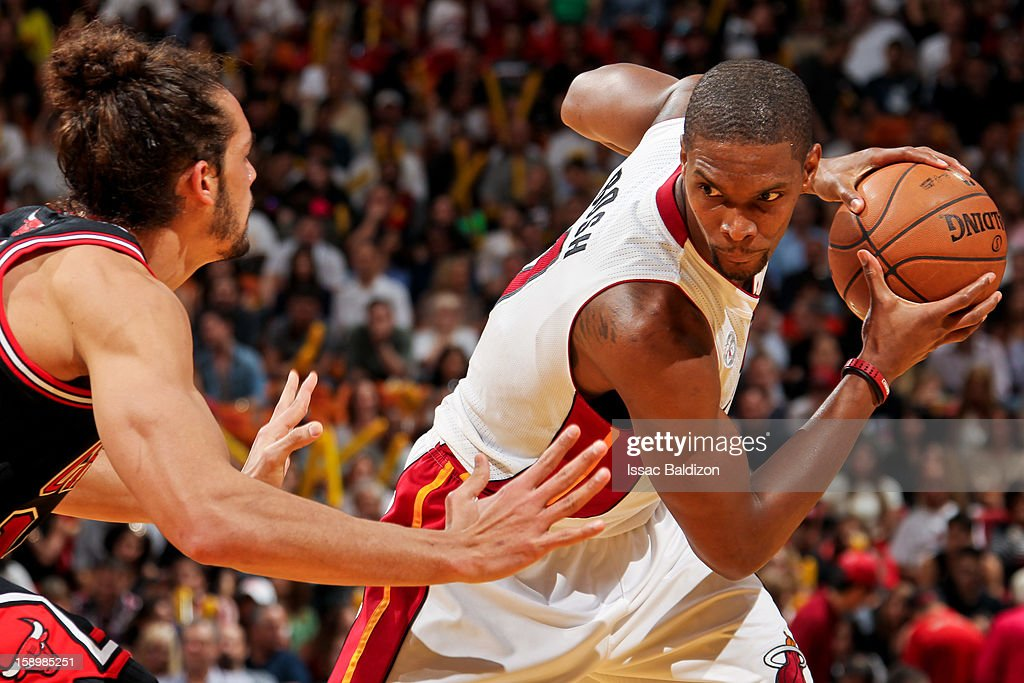 Chris Bosh #1 of the Miami Heat controls the ball against Joakim Noah #13 of the Chicago Bulls on January 4, 2013 at American Airlines Arena in Miami, Florida.