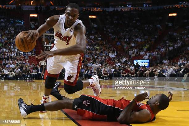 Chris Bosh of the Miami Heat dribbles the ball over Patrick Patterson of the Toronto Raptors at American Airlines Arena on March 31 2014 in Miami...
