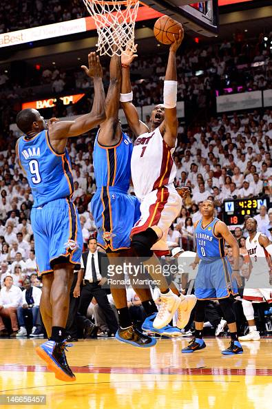 Chris Bosh of the Miami Heat drivers for a shot attempt in the first half against Serge Ibaka and Kendrick Perkins of the Oklahoma City Thunder in...