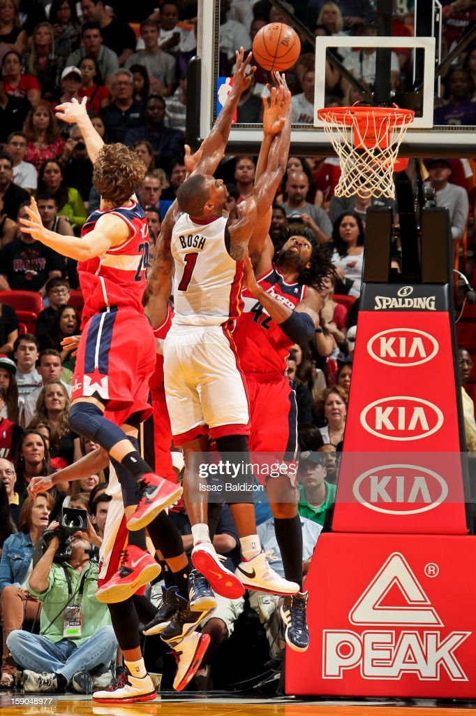 Chris Bosh #1 of the Miami Heat drives to the basket against Nene #42 and Jan Vesely #24 of the Washington Wizards on January 6, 2013 at American Airlines Arena in Miami, Florida.