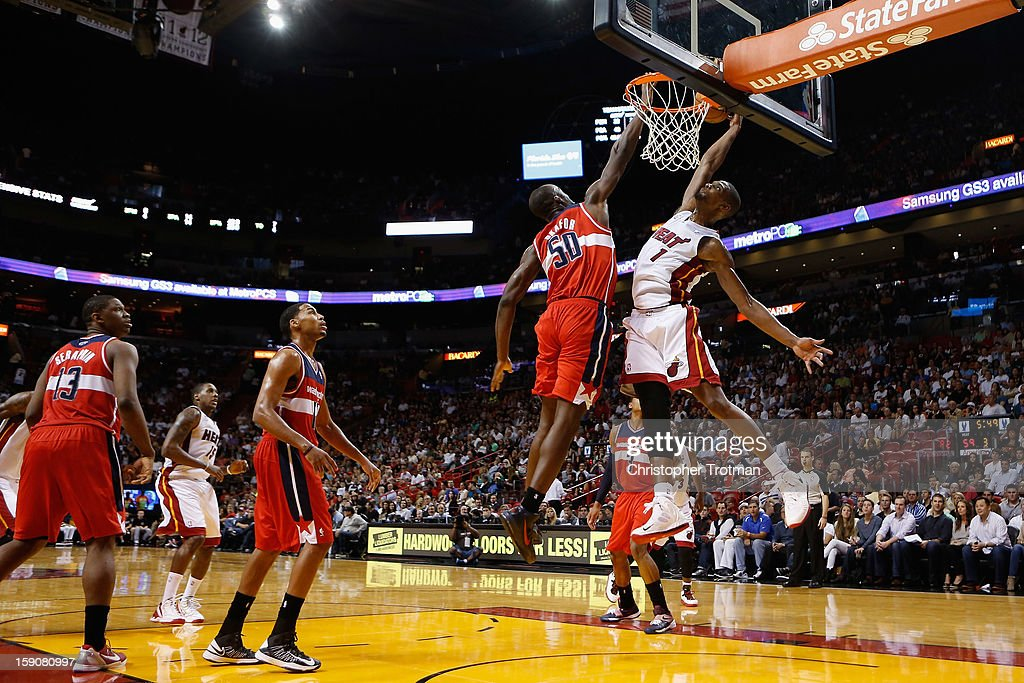 Chris Bosh #1 of the Miami Heat dunks the ball against (L) Emeka Okafor #50 of the Washington Wizards at American Airlines Arena on January 6, 2013 in Miami, Florida.