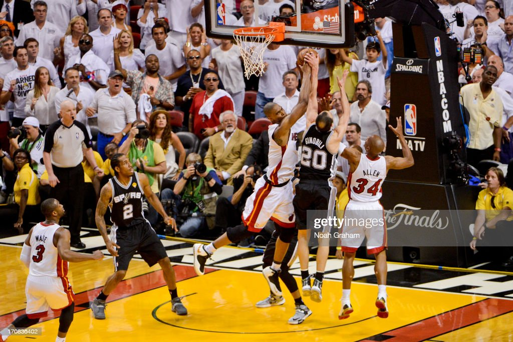 Chris Bosh #1 of the Miami Heat grabs a rebound late in the fourth quarter against Manu Ginobili #20 of the San Antonio Spurs, leading to a game-tying three-pointer by teammate Ray Allen #34 during Game Six of the 2013 NBA Finals on June 18, 2013 at American Airlines Arena in Miami, Florida.