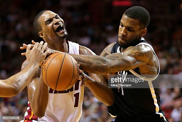 Chris Bosh of the Miami Heat has the ball stripped by Thomas Robinson of the Brooklyn Nets during a game at American Airlines Arena on December 28...