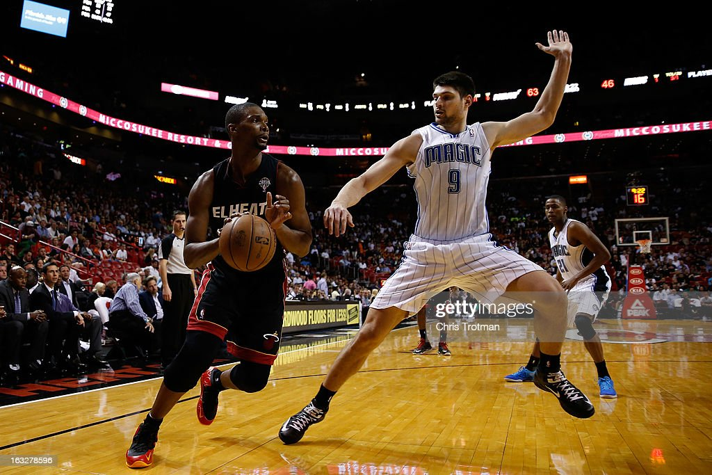 Chris Bosh #1 of the Miami Heat is guarded by Nikola Vucevic #9 of the Orlando Magic at American Airlines Arena on March 6, 2013 in Miami, Florida.