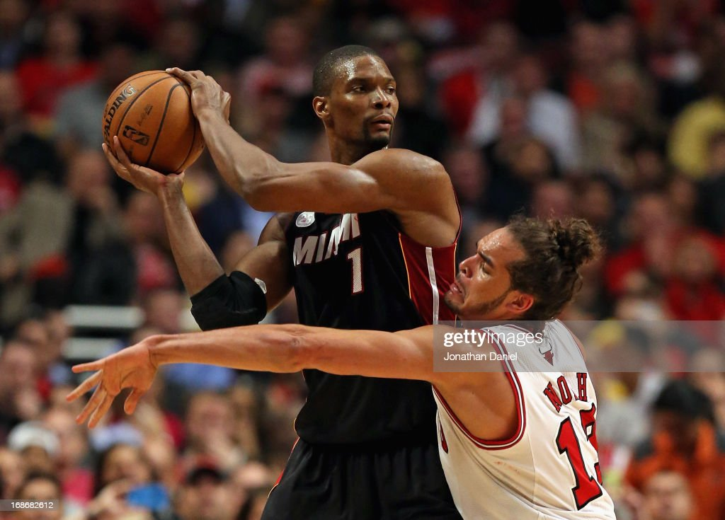 <a gi-track='captionPersonalityLinkClicked' href=/galleries/search?phrase=Chris+Bosh&family=editorial&specificpeople=201574 ng-click='$event.stopPropagation()'>Chris Bosh</a> #1 of the Miami Heat looks to pass against <a gi-track='captionPersonalityLinkClicked' href=/galleries/search?phrase=Joakim+Noah&family=editorial&specificpeople=699038 ng-click='$event.stopPropagation()'>Joakim Noah</a> #13 in Game Four of the Eastern Conference Semifinals during the 2013 NBA Playoffs at the United Center on May 13, 2013 in Chicago, Illinois. The Heat defeated the Bulls 88-65.