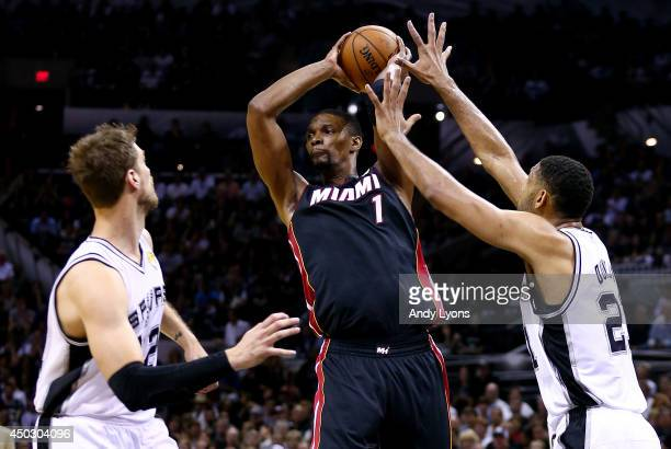 Chris Bosh of the Miami Heat looks to pass as Tiago Splitter and Tim Duncan of the San Antonio Spurs defend during Game Two of the 2014 NBA Finals at...