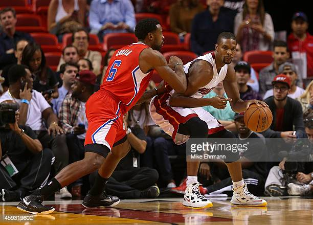 Chris Bosh of the Miami Heat posts up DeAndre Jordan of the Los Angeles Clippers during a game at American Airlines Arena on November 20 2014 in...