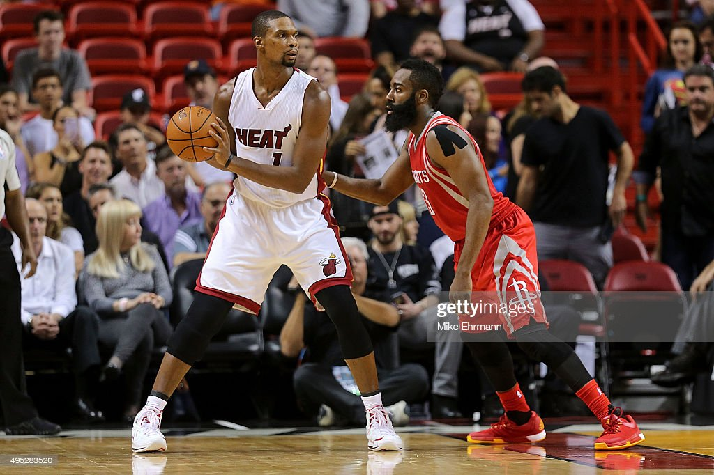 Chris Bosh of the Miami Heat posts up James Harden of the Houston Rockets during a game at American Airlines Arena on November 1 2015 in Miami...