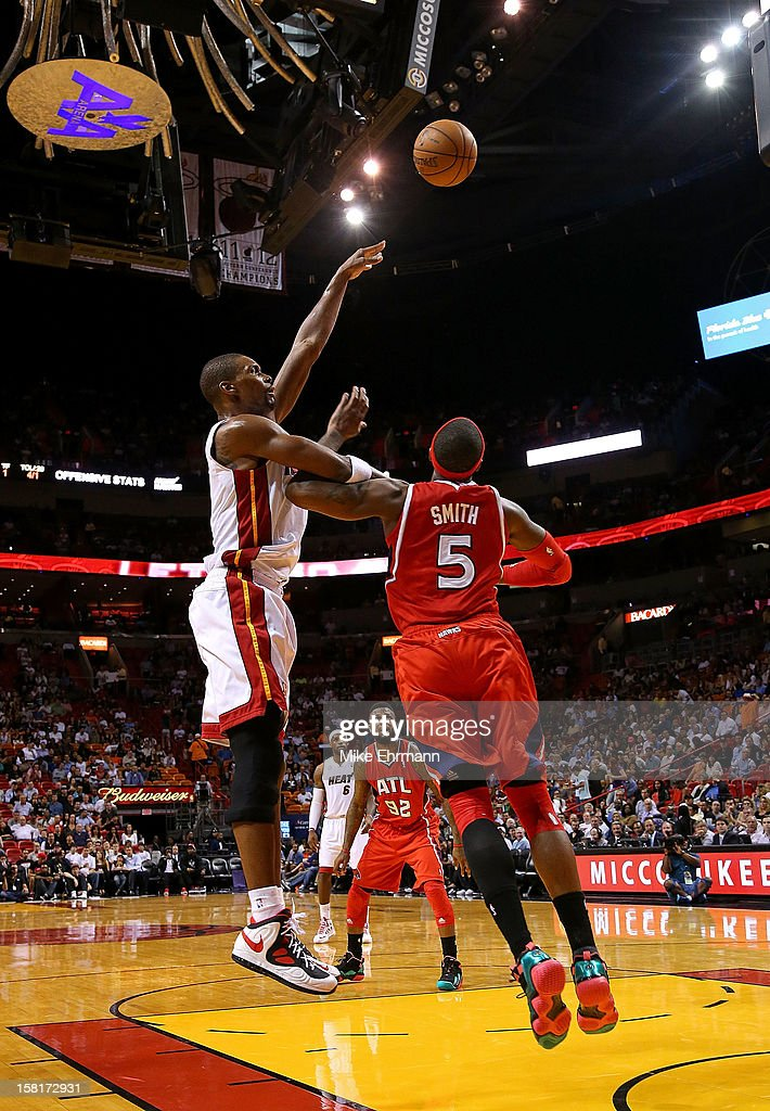 Chris Bosh #1 of the Miami Heat shoots over Josh Smith #5 of the Atlanta Hawks during a game at American Airlines Arena on December 10, 2012 in Miami, Florida.