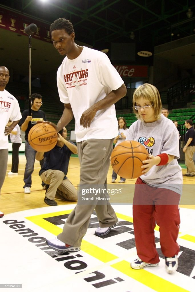 Chris Bosh of the Toronto Raptors works with a Special Olympics athlete during an NBA Cares clinic as part of the 2007 NBA Europe Live Tour at...