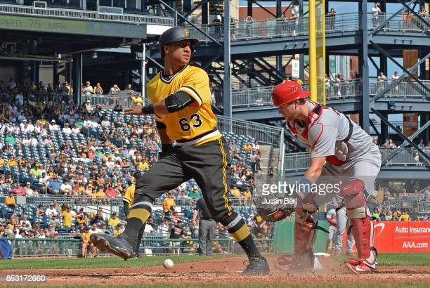 Chris Bostick of the Pittsburgh Pirates slides safely into home plate past Carson Kelly of the St Louis Cardinals in the third inning during the game...