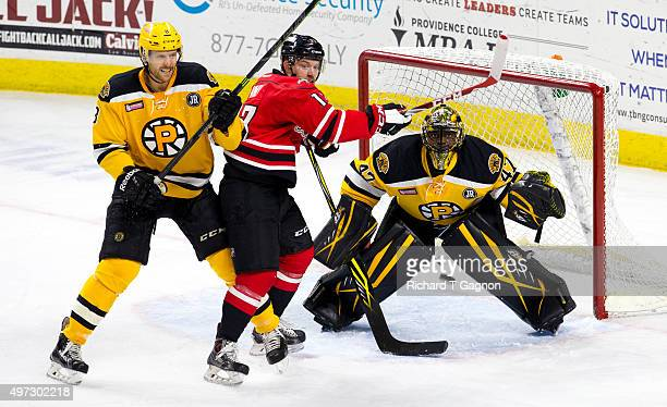 Chris Breen of the Providence Bruins battles for position against Derek Army of the Portland Pirates as Malcolm Subban watches the puck during an...