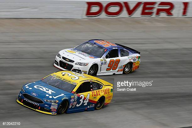 Chris Buescher driver of the CSX Play it Safe Ford races Timmy Hill driver of the Vydox Plus Chevrolet during the NASCAR Sprint Cup Series Citizen...