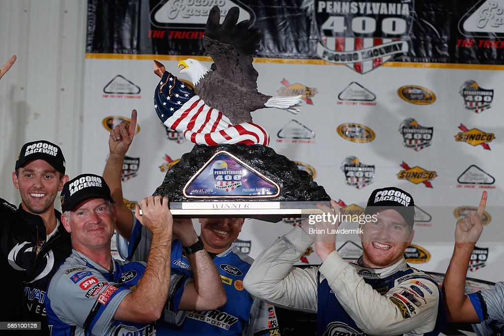 Chris Buescher, driver of the #34 Dockside Logistics Ford, and crew chief Bob Osborne pose with the trophy after winning the NASCAR Sprint Cup Series Pennsylvania 400 at Pocono Raceway on August 1, 2016 in Long Pond, Pennsylvania. The race was delayed due to inclement weather on Sunday, July 31.