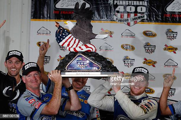 Chris Buescher driver of the Dockside Logistics Ford and crew chief Bob Osborne pose with the trophy after winning the NASCAR Sprint Cup Series...