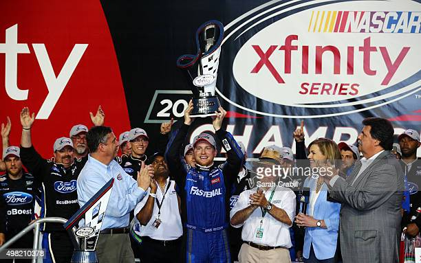 Chris Buescher driver of the Fastenal Ford celebrates winning the series championship with the trophy in Victory Lane during the NASCAR XFINITY...
