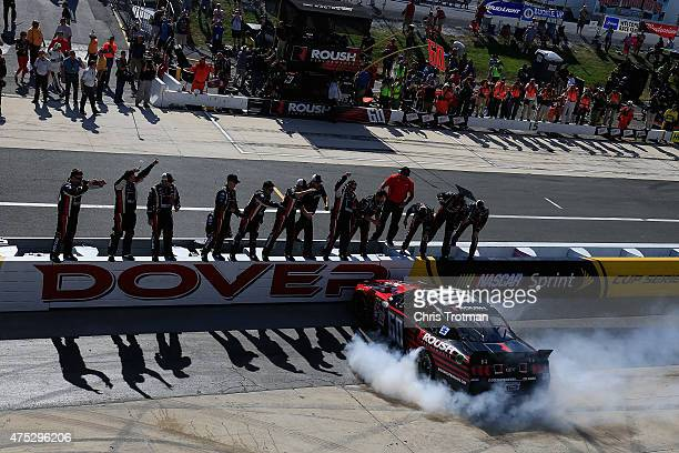 Chris Buescher driver of the Roush Performance Products Ford is cheered by his crew while celebrating with a burnout after winning the NASCAR XFINITY...