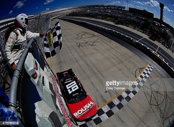 Chris Buescher driver of the Roush Performance Products Ford takes the checkered flag to win the NASCAR XFINITY Series Buckle Up 200 presented by...