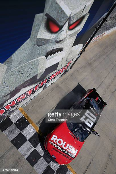 Chris Buescher driver of the Roush Performance Products Ford celebrates with the checkered flag after winning the NASCAR XFINITY Series Buckle Up 200...