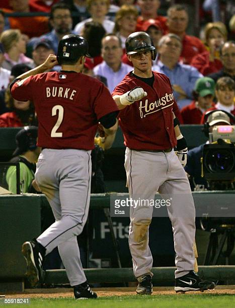 Chris Burke of the Houston Astros is congratulated by Craig Biggio after scoring on a wild pitch in the second inning against the St Louis Cardinals...