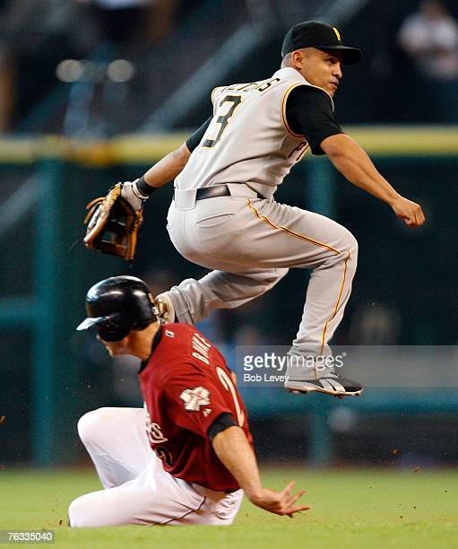 Chris Burke of the Houston Astros slides under shortstop Cesar Izturis of the Pittsburgh Pirates in an attempt to break up a double play during the...
