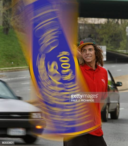Chris Butcher a 'spinner' with Arrow Advertising stands on a street in Arlington Virginia spinning his sign attracting attention from motorists...