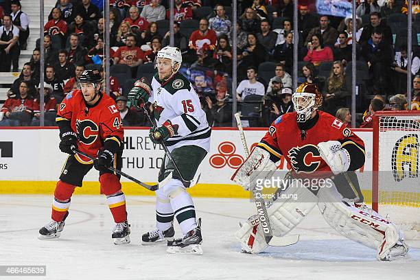 Chris Butler and Reto Berra of the Calgary Flames defend net against Dany Heatley of the Minnesota Wild during an NHL game at Scotiabank Saddledome...