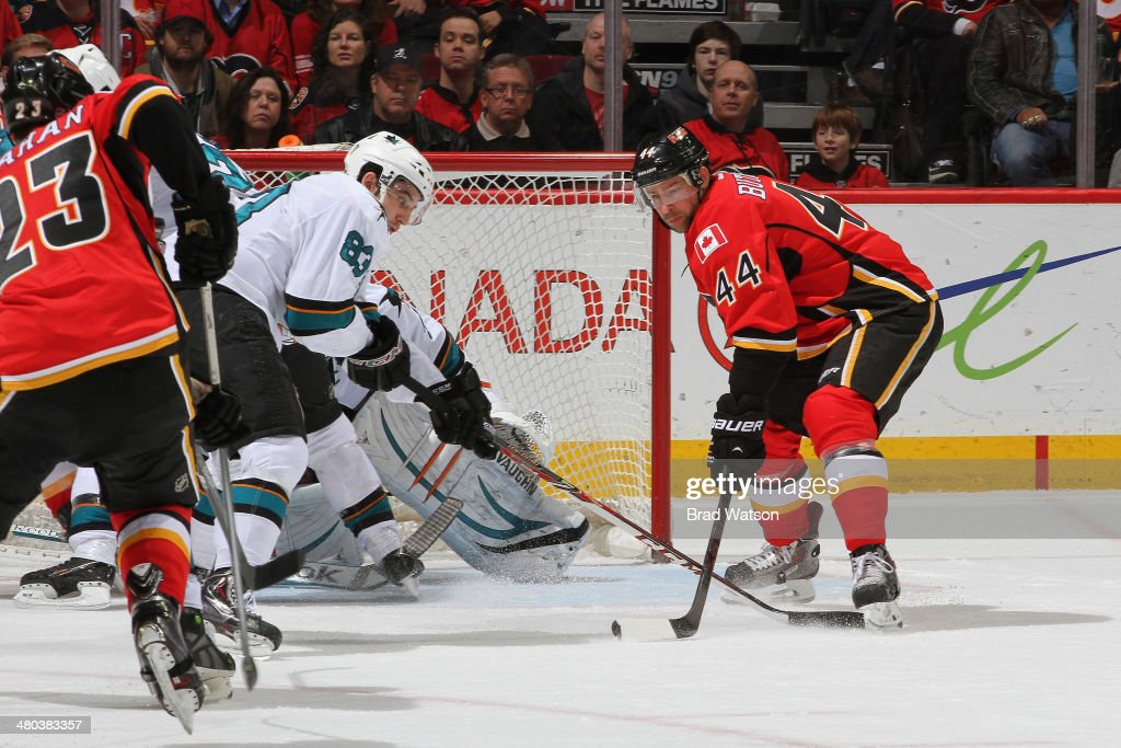 Chris Butler #44 and Sean Monahan #23 of the Calgary Flames skates against Matt Nieto #83 of the San Jose Sharks at Scotiabank Saddledome on March 24, 2014 in Calgary, Alberta, Canada.