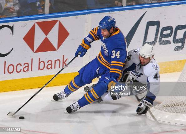 Chris Butler of the Buffalo Sabres skates ahead of Nate Thompson of the Tampa Bay Lightning at HSBC Arena on April 5 2011 in Buffalo New York