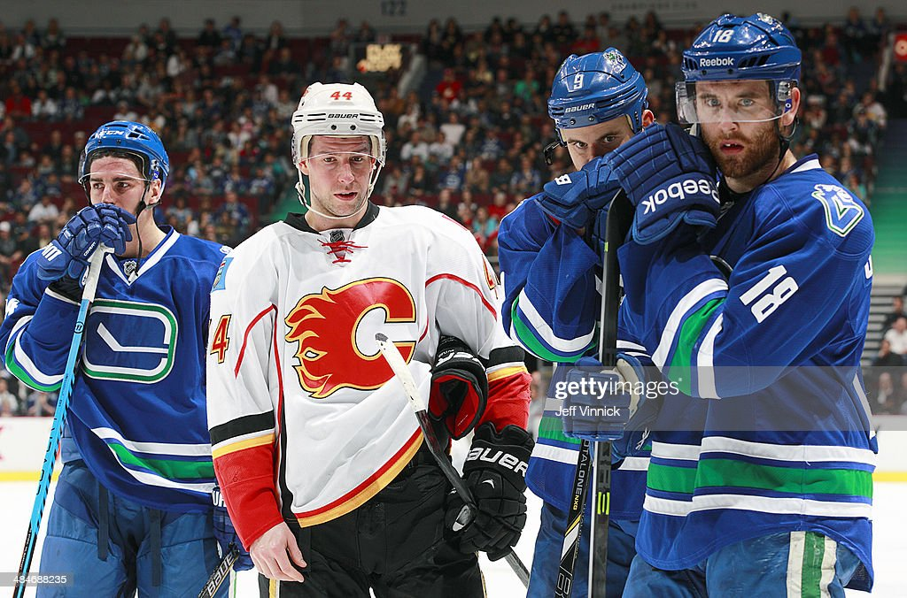 Chris Butler #44 of the Calgary Flames, Alexandre Burrows #14, Zack Kassian #9 and Ryan Stanton #18 of the Vancouver Canucks watch with concern as Daniel Sedin #22 of the Canucks receives medical attention during their NHL game at Rogers Arena April 13, 2014 in Vancouver, British Columbia, Canada.
