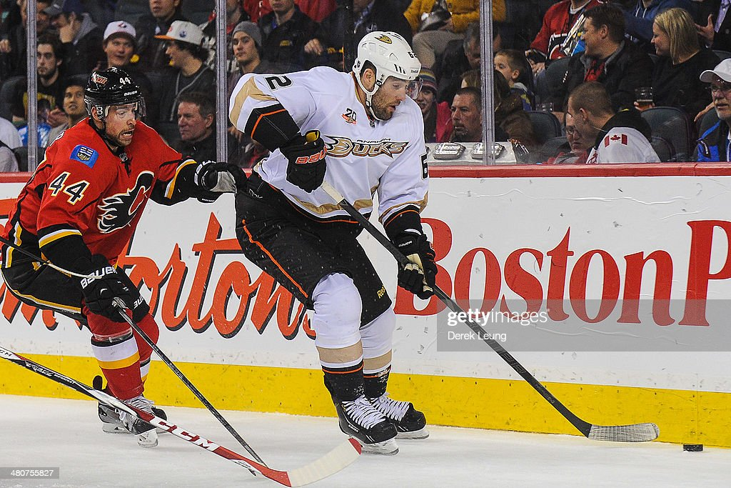 Chris Butler #44 of the Calgary Flames chases Patrick Maroon #62 of the Anaheim Ducks during an NHL game at Scotiabank Saddledome on March 26, 2014 in Calgary, Alberta, Canada.