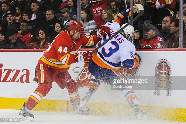 Chris Butler of the Calgary Flames checks Casey Cizikas of the New York Islanders during an NHL game at Scotiabank Saddledome on March 7 2014 in...