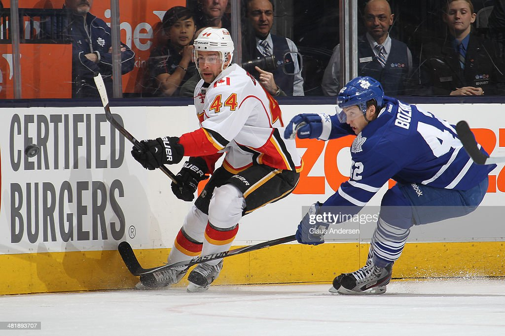 Chris Butler #44 of the Calgary Flames clears the puck against Tyler Bozak #42 of the Toronto Maple Leafs during an NHL game at the Air Canada Centre on April 1, 2014 in Toronto, Ontario, Canada.