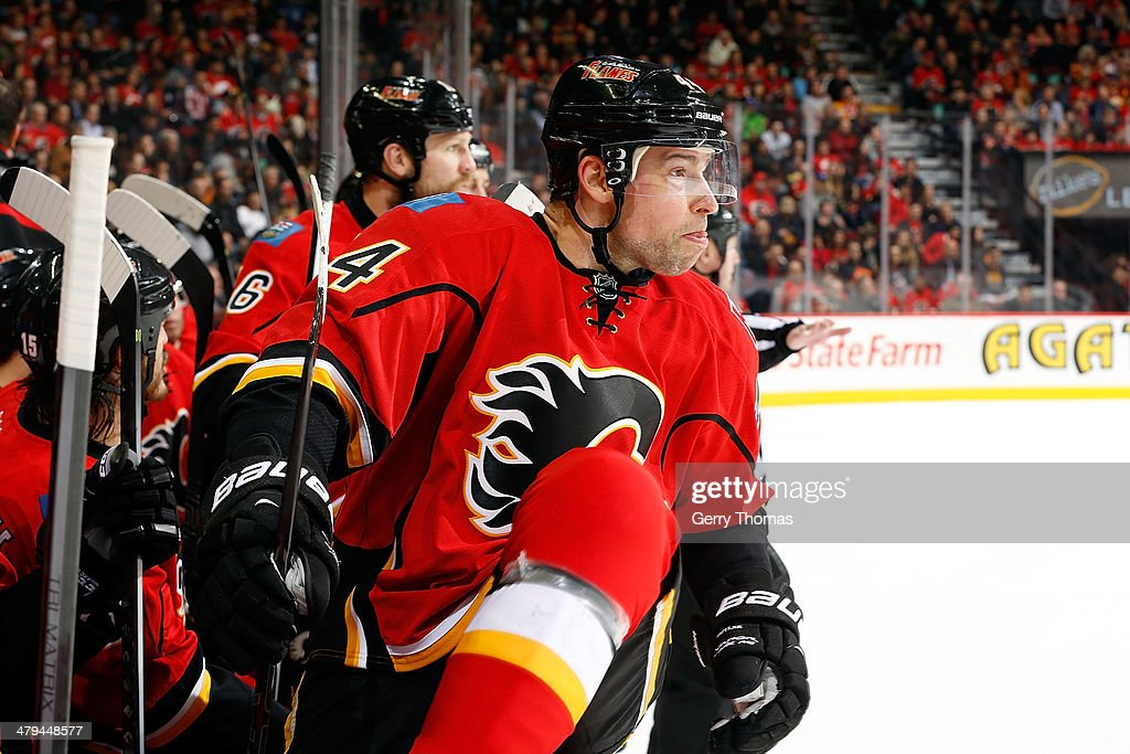 Chris Butler #44 of the Calgary Flames jumps over the bench for a shift against the Buffalo Sabres at Scotiabank Saddledome on March 18, 2014 in Calgary, Alberta, Canada.