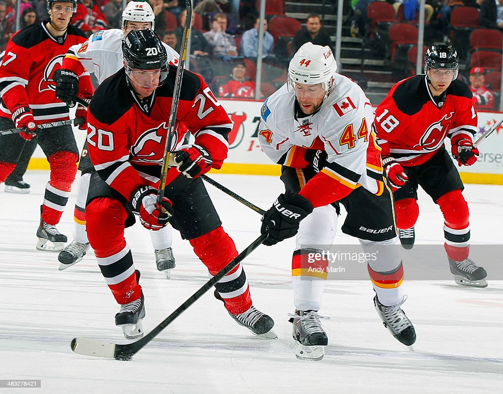 Chris Butler #44 of the Calgary Flames plays the puck while being defended by Ryan Carter #20 of the New Jersey Devils during the game at the Prudential Center on April 7, 2014 in Newark, New Jersey. (Photo by Andy Marlin/NHLI via Getty Images.