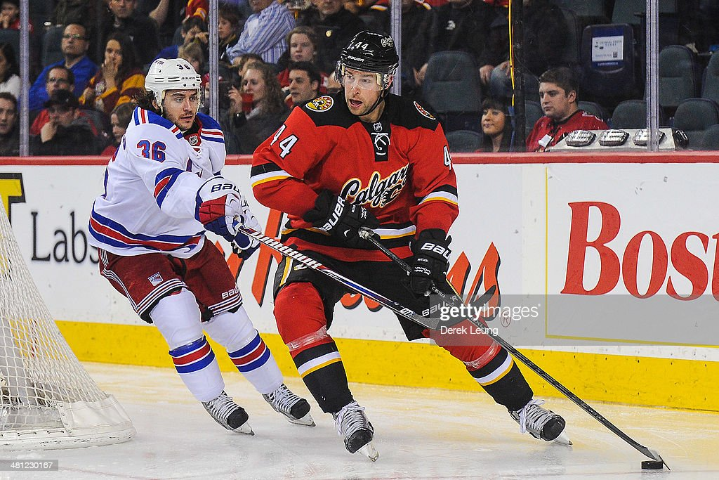 Chris Butler #44 of the Calgary Flames skates with the puck against Mats Zuccarello #36 of the New York Rangers during an NHL game at Scotiabank Saddledome on March 28, 2014 in Calgary, Alberta, Canada. The Flames defeated the Rangers 4-3.