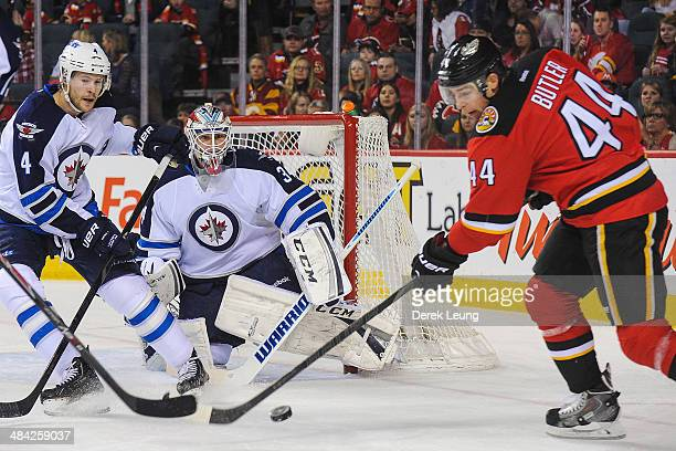 Chris Butler of the Calgary Flames takes a shot on Michael Hutchinson of the Winnipeg Jets during an NHL game at Scotiabank Saddledome on April 11...