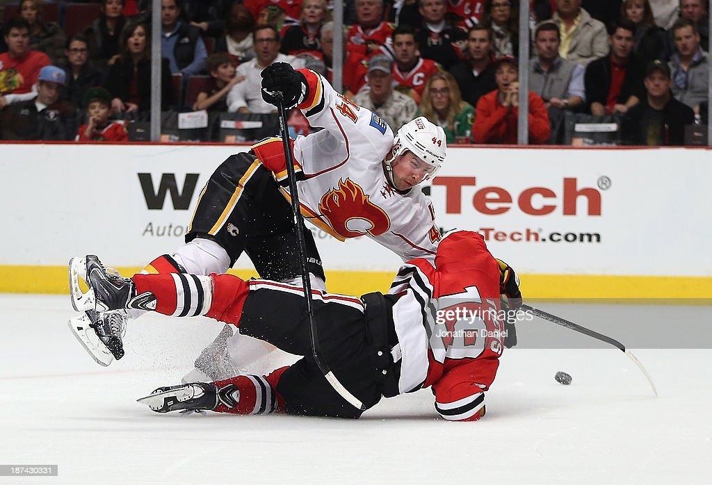 Chris Butler #44 of the Calgary Flames takes down <a gi-track='captionPersonalityLinkClicked' href=/galleries/search?phrase=Jonathan+Toews&family=editorial&specificpeople=537799 ng-click='$event.stopPropagation()'>Jonathan Toews</a> #19 of the Chicago Blackhawks for a penalty at the United Center on November 3, 2013 in Chicago, Illinois. The Flames defeated the Blackhawks 3-2 in overtime.