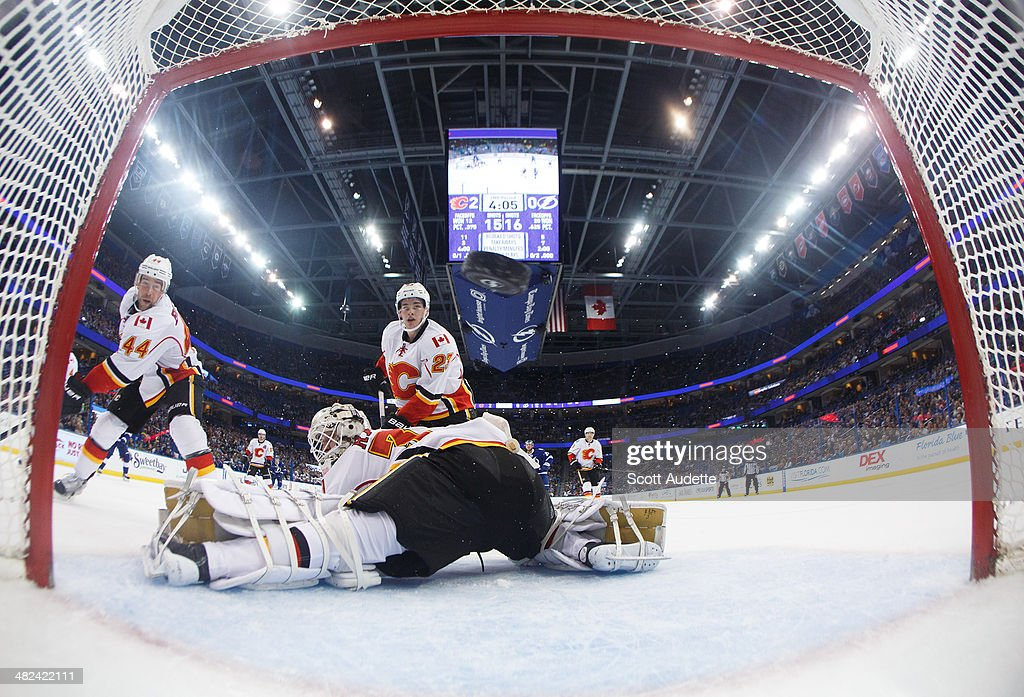 Chris Butler #44, Sean Monahan #23, and goalie Karri Ramo #31 of the Calgary Flames watch the puck go into the net for a goal for the Tampa Bay Lightning during the second period at the Tampa Bay Times Forum on April 3, 2014 in Tampa, Florida.
