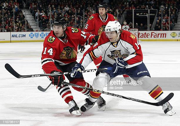 Chris Campoli of the Chicago Blackhawks and Sergei Samsonov of the Florida Panthers skate after the puck as Fernando Pisani of the Blackhawks watches...